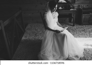 Beautiful bride reading letter from the groom for love. Bride's tears of happiness, joy. The bride sits at window and reads letter to groom. Wedding vows. Morning of the bride. Black and white photo.