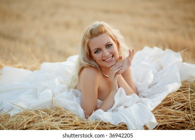 Beautiful bride relaxing in hay stack at her wedding day