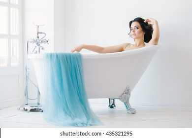 Beautiful bride relaxing in the tub. Wedding dress colors serenity white Studio. With makeup and hair.
