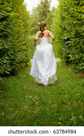 Beautiful bride running in the garden