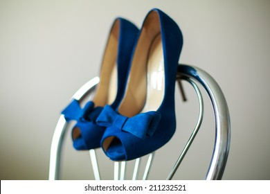 beautiful bride shoes with a gorgeous bow hanging on the back of a chair  girl in shoes with high heels   pair of blue shoes with heels  shoes on a chair indoor close up.
