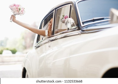 Beautiful bride sits with wedding bouquet in a retro car and has fun