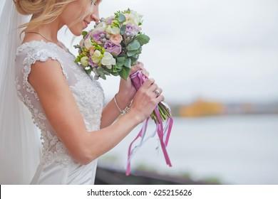 Beautiful bride smelling wedding bouquet close up