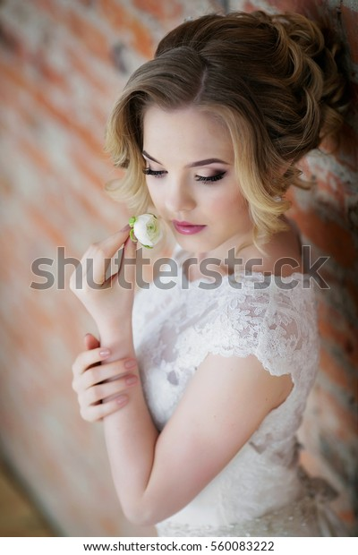 beautiful bride smelling a white flower