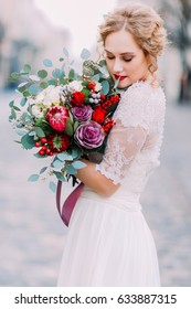 Beautiful bride softly holds wer vintage wedding bouquet with ancient european architecture on background