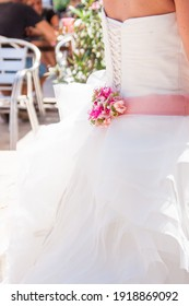Beautiful bride, standing back, open shoulders white dress, pink belt and flowers