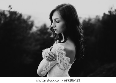 A beautiful bride standing on a cliff at sunset