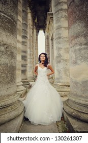 beautiful bride stands between the  columns of the an old church in west Ukraine