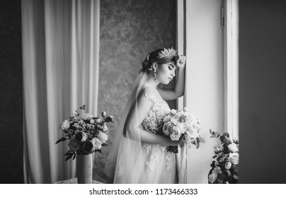 A beautiful bride stands by the window. Stylish bride in a lace dress. Wedding flowers. Black and white photography.