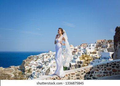 Beautiful bride stands at a high level above the sea on the background of architecture of Santorini, Greece
