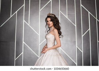 A beautiful bride stands in a lush wedding dress indoors. The bride in the crown. Dark lips. Lush dress.  Black background with white stripes.