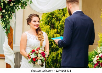 A beautiful bride stands near the decorated arch and holds a wedding bouquet. the groom in a beautiful costume reads the vow of the bride