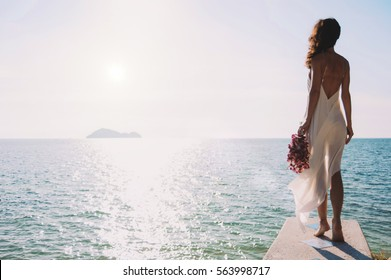 beautiful bride stands on a cliff above the sea