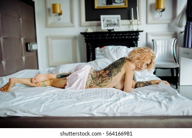 Beautiful bride with tattoo in lingerie showing sexy pose leaning at bed over her bedroom. Color. Sexual memories. Pictures on spin.