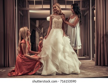 Beautiful bride is trying on an elegant wedding dress in modern wedding salon, her friends are helping