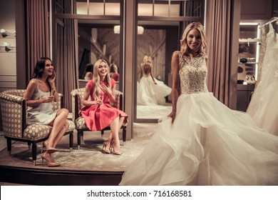 Beautiful bride is trying on an elegant wedding dress in modern wedding salon, her friends are drinking champagne, smiling and admiring