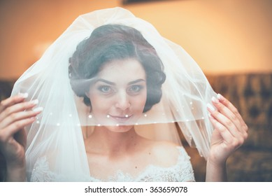 beautiful bride with a veil on her head and looks in the frame smiles, happiness, love