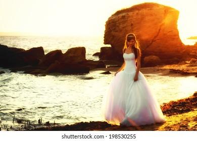 Beautiful bride walking along the seaside at sunset