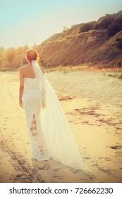 Beautiful bride walking on beach