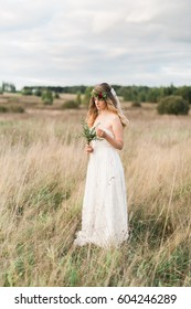 Beautiful bride wearing a natural flower wreath and standing in the golden summer fields with eucalyptus in hands.
