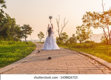 Beautiful bride wearing a white wedding dress running away alone in nature outdoor with throw a bouquet of flowers and shoes on the street. Runaway bride before wedding ceremony concept.