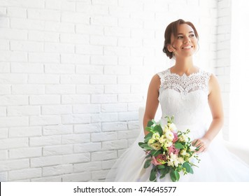Beautiful bride with wedding bouquet on white brick wall background