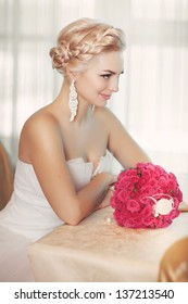 Beautiful bride at wedding day with rink roses bouquet wedding flowers at restaurant waiting for groom/ Happy stylish woman in bridal white dress in cafe/ Girl in love wt marriage day