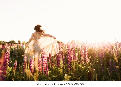 A beautiful bride in wedding dress dancing alone in field of lupine flowers on sunset. View from the back