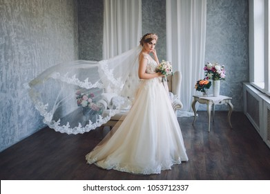 Beautiful bride in wedding dress with lace. The wedding veil flies like in the wind. Studio. Interior.