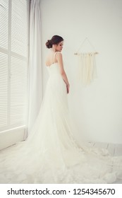 Beautiful bride in wedding dress in light room