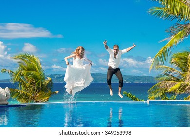 Beautiful bride in wedding dress with long train and groom jumping in the infinity pool in the hotel on a tropical island. Wedding and honeymoon.