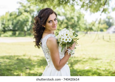 Beautiful bride in wedding dress outdoor in a field at sunset