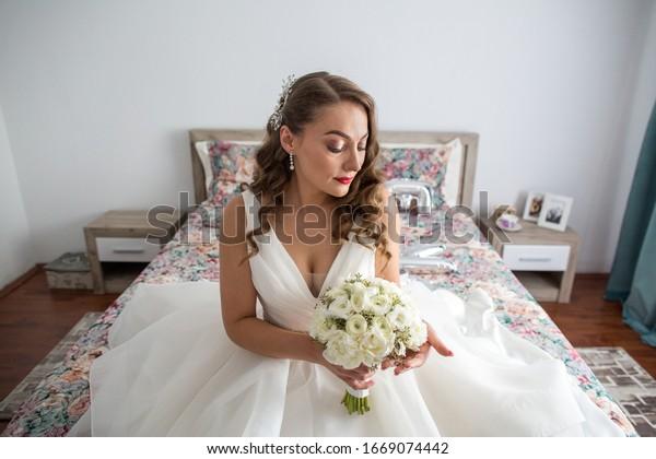 ベッドに座っているウエディングドレスを着た美しい花嫁