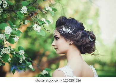 Beautiful bride with wedding flowers, attractive woman in wedding dress. Bride with wedding makeup and hairstyle.