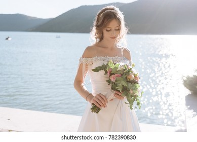 Beautiful bride with wedding flowers bouquet, attractive woman in wedding dress.