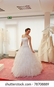 Beautiful bride in a wedding gown in the bridal shop.