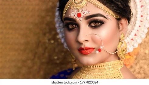 Beautiful bride with wedding makeup and jewelry .Indian Bridal fashion model with open eyes posing in interior.