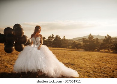 Beautiful bride in white dress with black balloons at sunset