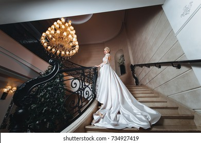 Beautiful bride in a white dress with long train is climbs up the stairs in a classic interior.