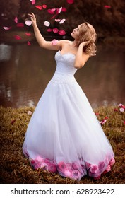 Beautiful bride in white dress with pink and red flowers, park