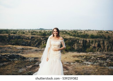 beautiful bride in a white dress stands outdoors