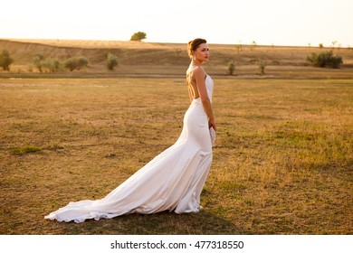 Beautiful bride in white dress with a train