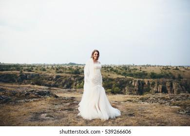beautiful bride in a white dress walking on the field