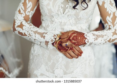 Beautiful bride in a white dress. Woman with gold bracelets. Lady with mehendi on her hands