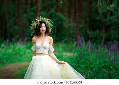 Beautiful bride in a white dress with a wreath of flowers