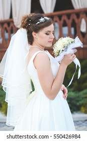 beautiful bride in a white lush dress walks outdoors