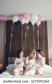 Beautiful bride in a white pajamas. Ladies in a hotel room. Women sitting on a beg. Girls drinking champagne