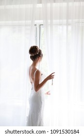 Beautiful bride in white wedding dress standing in her bedroom and looking in window. Bride holding a glass of champagne. Beautiful bride