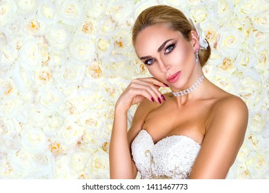 beautiful bride in white wedding dress on the background of a wall of flowers. - Image