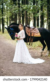 Beautiful bride in a white wedding dress stands near a black horse, vertical photo, wedding bouquet, cute look, designer wedding dress with a train, country wedding, preparation for meeting the groom